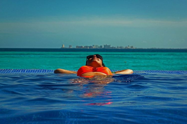 Young Woman Resting In Infinity Pool Against Sky