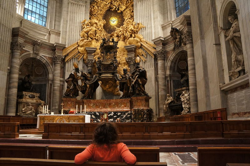 Rear view of woman sitting in st peters basilica