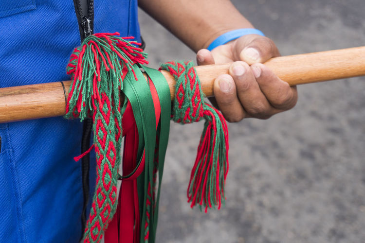 Midsection of person holding bamboo with ribbons