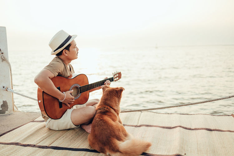 Side view of man playing guitar while sitting with dog at pier against sea