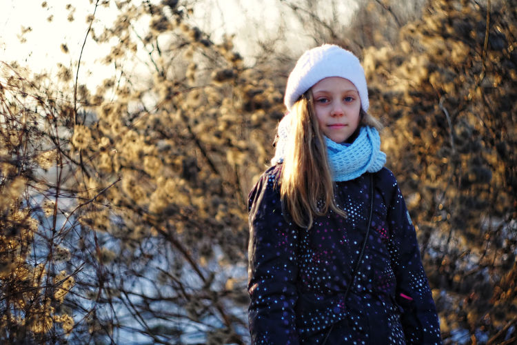Portrait of girl against dried plants during winter
