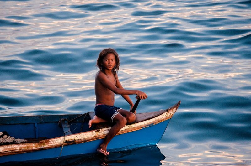 Man Looking Away While Sitting On Boat In Sea