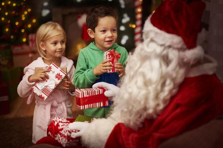 Santa Claus Giving Gifts To Siblings At Home