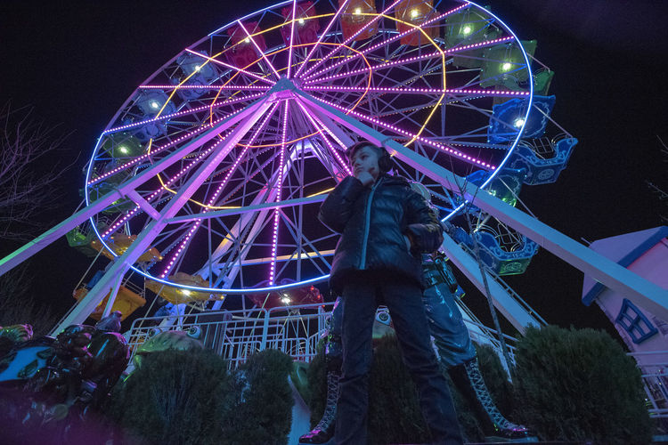 Arts Culture And Entertainment Illuminated Amusement Park Night Amusement Park Ride Leisure Activity Real People Ferris Wheel Sky Low Angle View Architecture One Person Built Structure Standing Lifestyles Glowing Outdoors Nature Enjoyment Light Fairground