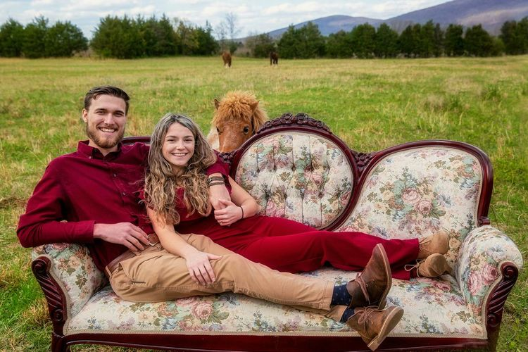 Portrait of a smiling young couple sitting on grass