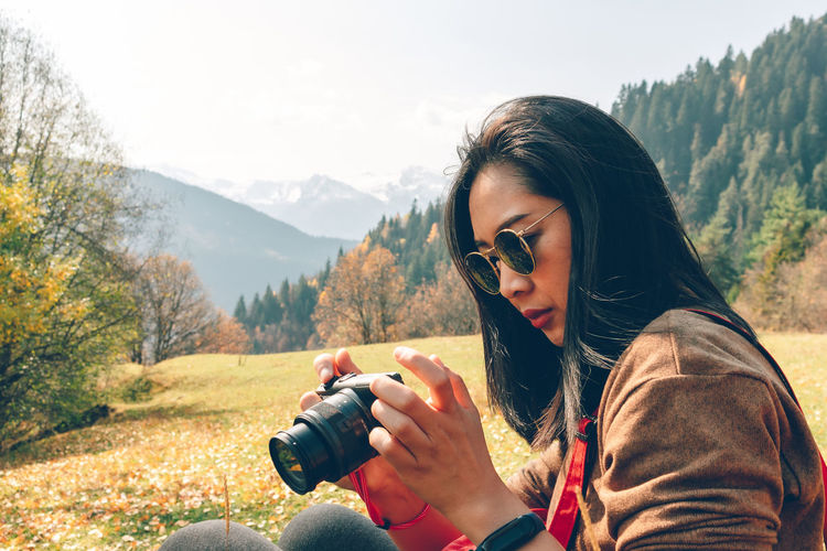 Woman photographing against mountains