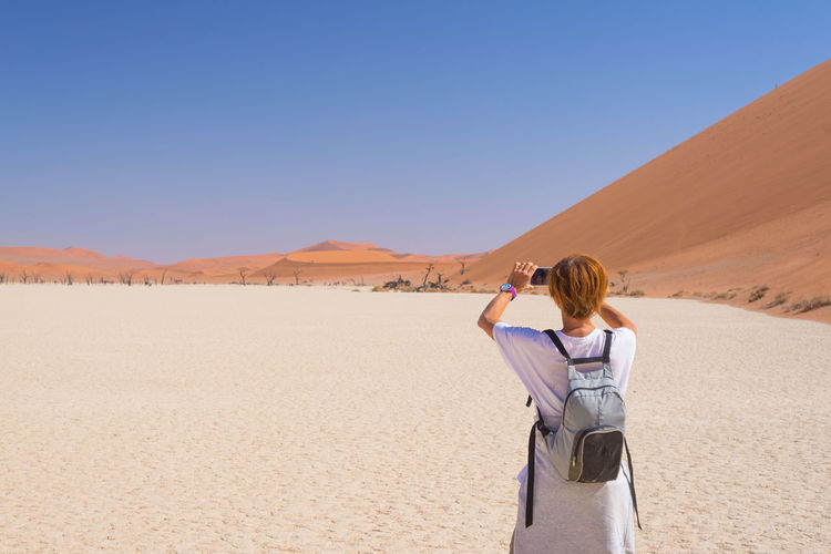 Rear view of mature woman photographing at desert