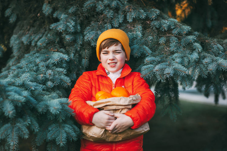 A cute boy in a bright orange jacket and a yellow hat holds a large package with oranges in his hand
