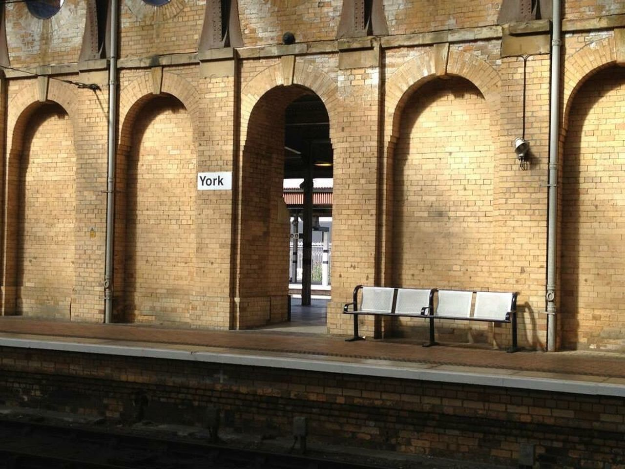 architecture, built structure, arch, building exterior, no people, building, day, wall, brick wall, city, outdoors, communication, window, wall - building feature, seat, railroad station, rail transportation, absence, brick, text, arched
