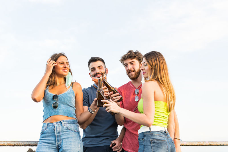 Carefree young friends standing with beer bottle against sky