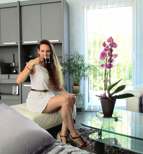 Full Length Of Young Woman Drinking Black Coffee While Sitting At Home