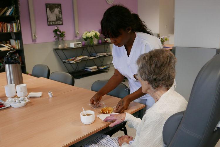 Caretaker serving breakfast to senior woman in nursing home