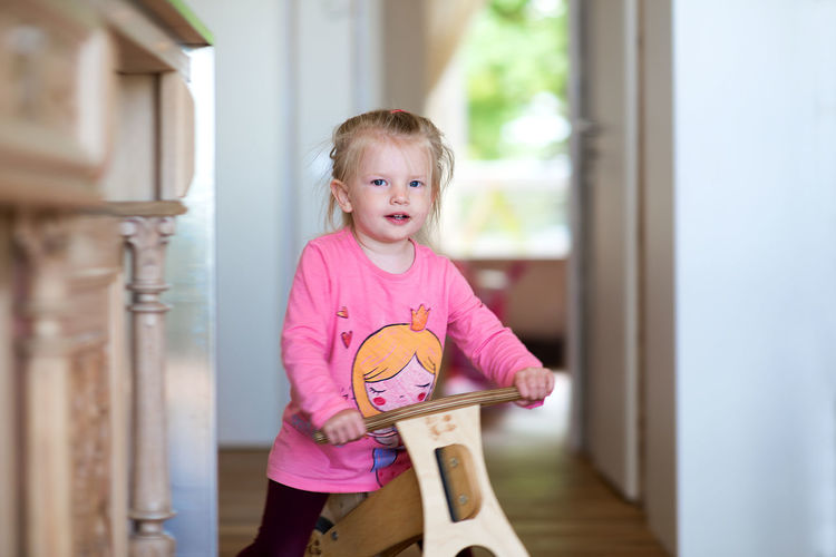 Beautiful portrait of blonde little girl Children Fun Funny Happy Happy People Home Kids Pink Princess Blond Hair Child Childhood Day Family Life Home Interior Indoors  Kid Little Girl One Person People Portrait Real People Smiling Toddler  Wooden Bicycle