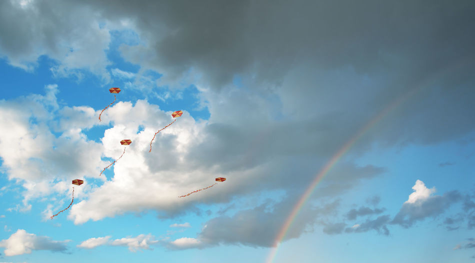 Flying kites in a sky with clouds and a rainbow