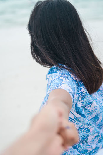 Side view of woman holding person hand at beach