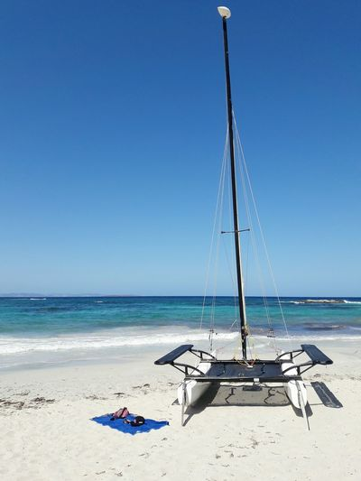 Outrigger boat at beach against clear blue sky