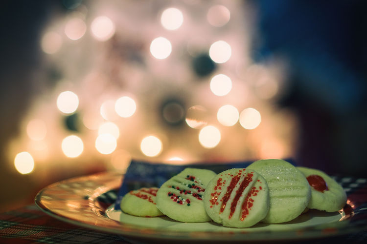 Close-up of sweet food in plate on table against christmas tree