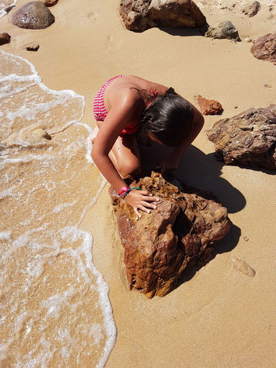 High angle view of girl crouching by rock on shore at beach