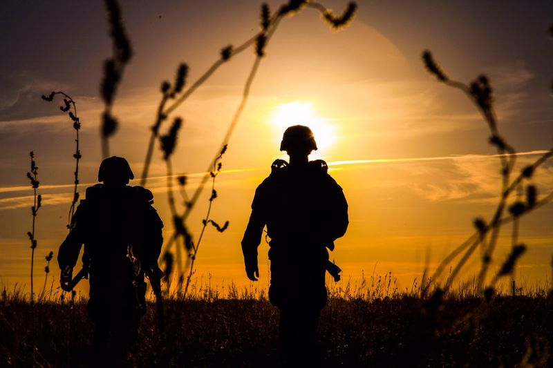 Silhouette army soldiers against sunset