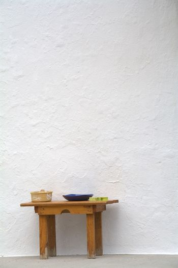 Container And Plate On Wooden Table Against White Wall
