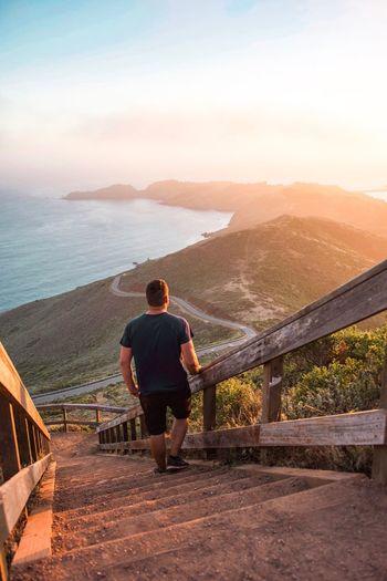 Rear view of man standing on footbridge over sea against sky