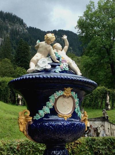 This lovely porcelain vase is so gorgeous set against the natural landscape in Linderhof Castle. Art Cupid Nature Outdoors Porcelain  Sculpture Statue Vase
