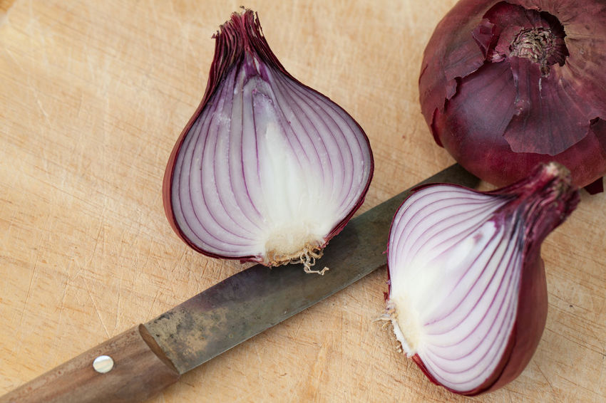 One whole and two half red onions on a cutting board with a kitchen knife Red Close-up Cutting Board Food Food And Drink Freshness Healthy Eating High Angle View Indoors  Ingredient Kitchen Knife No People Onion Raw Food Spice Still Life Table Vegetable Wellbeing