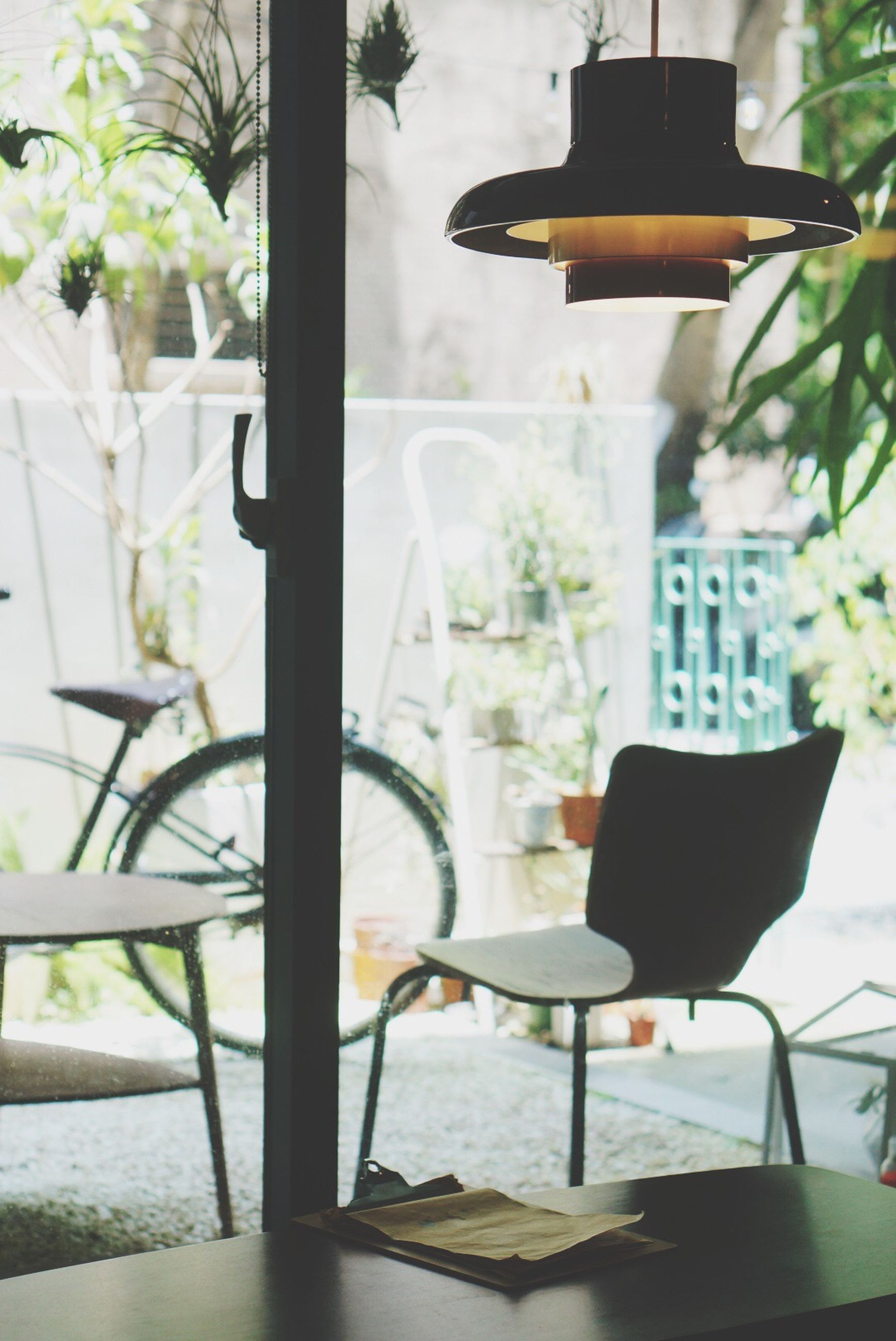chair, table, potted plant, indoors, absence, home interior, plant, vase, sunlight, furniture, restaurant, window, empty, growth, flower pot, sidewalk cafe, seat, front or back yard, house, no people