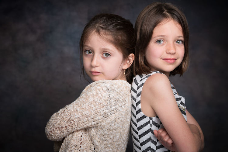 Portrait of girls with arms crossed standing back to back against wall
