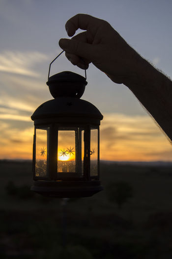 A lantern of sunset light Human Hand Human Body Part Hand Sunset One Person Sky Real People Holding Silhouette Orange Color Unrecognizable Person Body Part Transparent Glass - Material Cloud - Sky Nature Men Lifestyles Finger