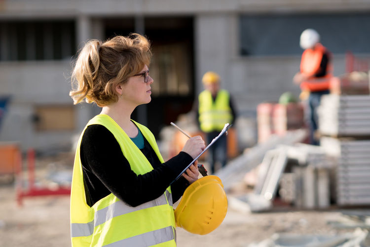 Female engineer writing on clipboard at construction site