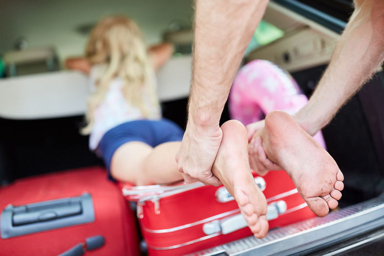 Cropped hand of man pulling legs of girl from car