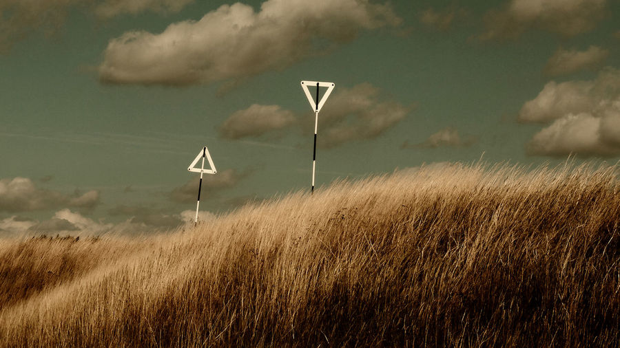 Wind turbines in field against sky