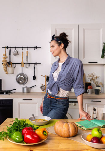 Young woman preparing food on table at home