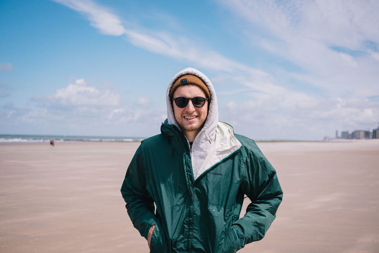 Portrait of smiling young man standing on beach
