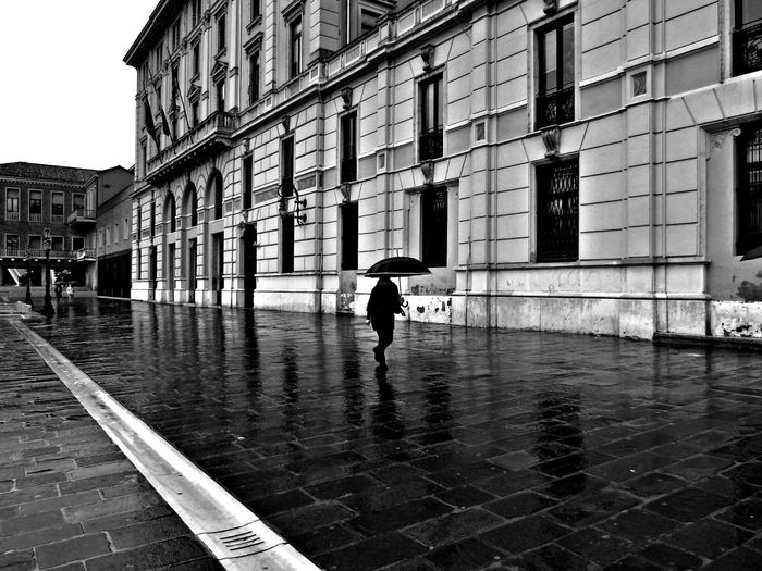 Person with umbrella walking on wet street by building