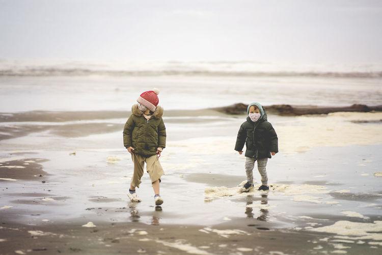 Full length of kids wearing mask walking on beach against sky