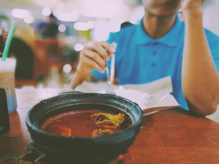 Close-up of asam pedasin bowl on table against man at restaurant