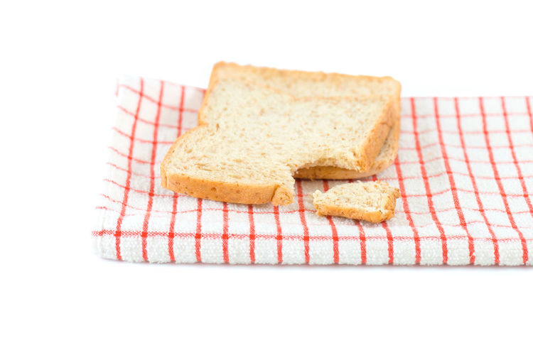 Bitten sliced bread on towel ,isolated white background. A bite taken out of a sliced whole wheat and organic ingredient bread,healthy eating concept. Breakfast Hungry Bitten Bread Bread Healthy Eating Healthy Lifestyle Isolated White Background Sliced Bread Whole Wheat Bread