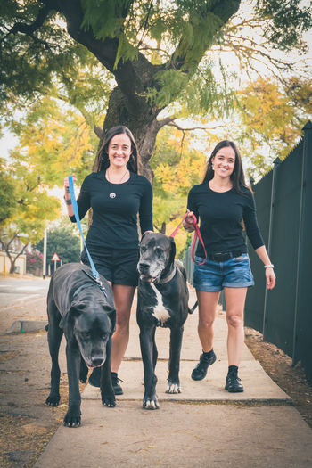 Portrait of smiling sisters with dog walking on footpath against trees