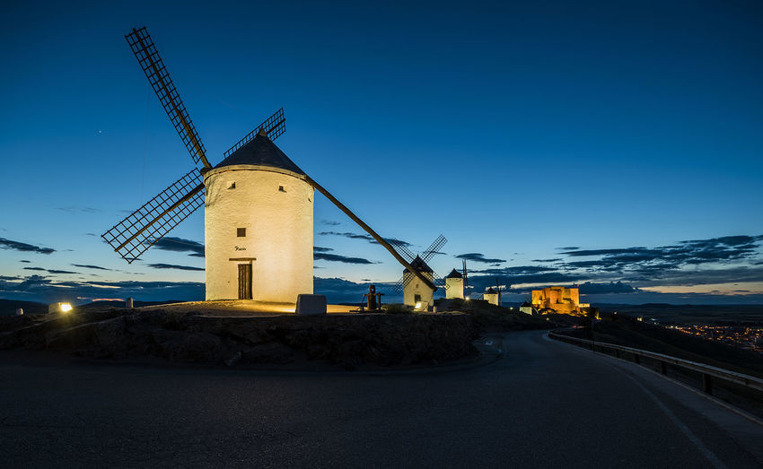 Quixote Windmills Alternative Energy Architecture Blue Building Exterior Built Structure Clear Sky Dusk Environment Environmental Conservation Fuel And Power Generation Nature No People Outdoors Renewable Energy Road Sky Technology Traditional Windmill Transportation Turbine Wind Power Wind Turbine