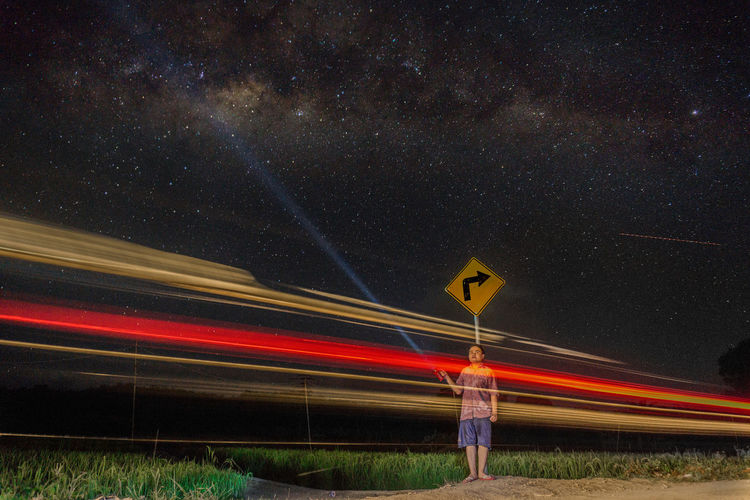 Man Holding Torch While Standing By Light Trails Against Star Field