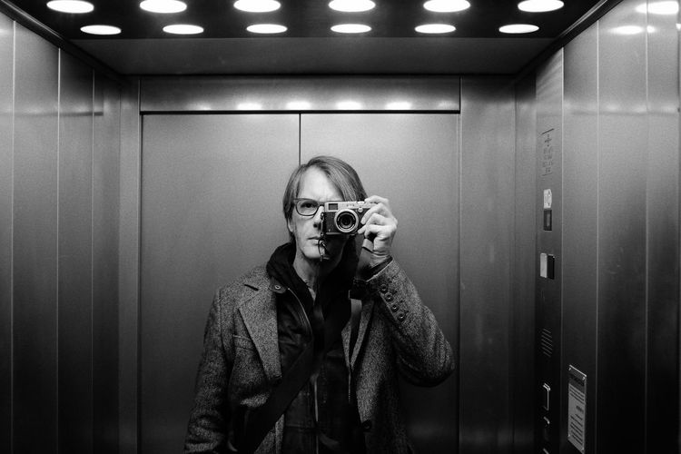 Portrait of man photographing in elevator