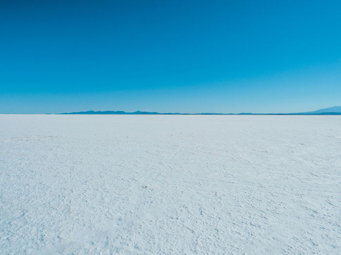 Salt flats for miles Arid Climate Beauty In Nature Blue Clear Sky Climate Copy Space Day Desert Environment Horizon Horizon Over Land Land Landscape Mineral Nature No People Salt Flat Scenics - Nature Sky Tranquil Scene Tranquility