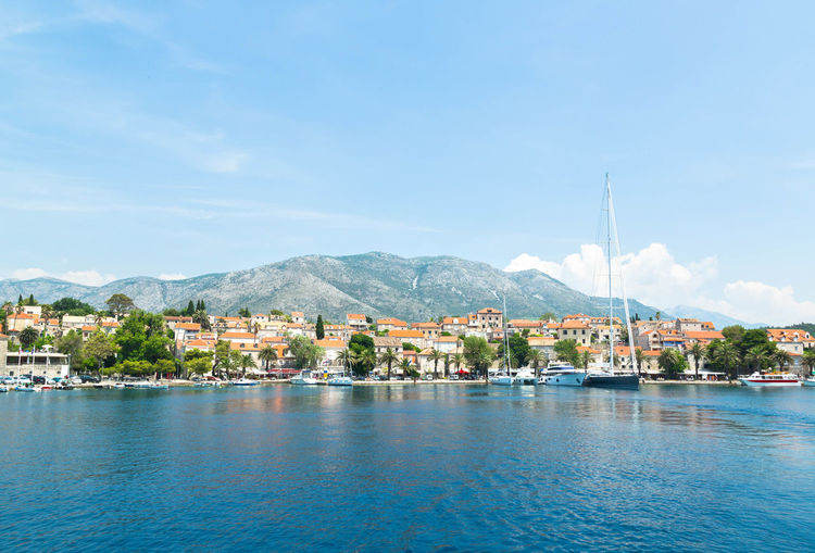 Sailboats Moored On Adriatic Sea By Houses Against Sky At Cavtat
