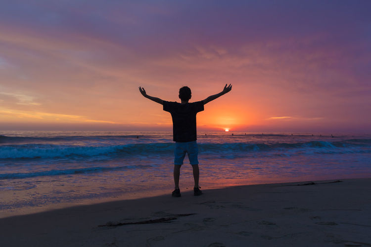 Rear View Of Man With Arms Outstretched Standing Against Sea During Sunset