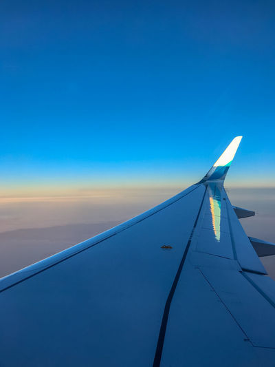 Close-up of airplane wing against clear blue sky