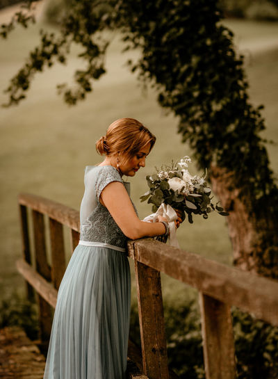 Bridesmaid, alone, lonely, holding bouquet.