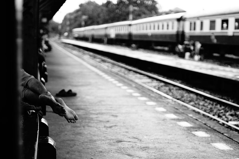 Low section of man lying on seat at railroad station platform