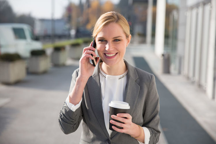 Businesswoman Holding Coffee While Talking On Smart Phone